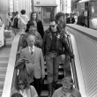 A black and white photograph of Stannous Flouride, wearing sunglasses and a leather jacket and boots, walking down the escalator at Montgomery BART station, surrounded by business people wearing suits.